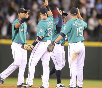 SEATTLE - AUGUST 15:  Trayvon Robinson #12 (2R) of the Seattle Mariners celebrates with Kyle Seager #15, Mike Carp #20, and Franklin Gutierrez #21 after defeating the Toronto Blue Jays 6-5 at Safeco Field on August 15, 2011 in Seattle, Washington. (Photo