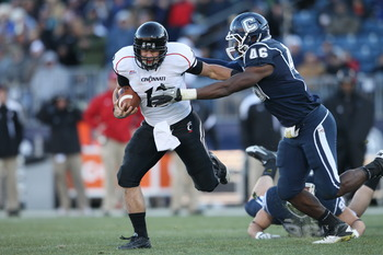 EAST HARTFORD, CT - NOVEMBER 27:  Zach Collaros #12 of the Cincinnati Bearcats carries the ball as Sio Moore #46 of the Connecticut Huskies makes the tackle on November 27, 2010 at Rentschler Field in East Hartford, Connecticut. The Huskies defeated the B