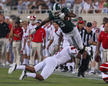 EAST LANSING, MI - SEPTEMBER 02: Mike Sadler #3 of the Michigan State Spartans is leg tackled by Josh Garner #1 of the Youngstown State Penguins during an NCAA football game at Spartan Stadium on September 2, 2011 in East Lansing, Michigan. The Spartans w