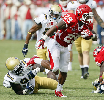 HOUSTON - SEPTEMBER 03:  Running back Michael Hayes #29 of the Houston Cougars breaks the tackle of  defensive end Owamagbe Odighizuwa #94 of UCLA at Robertson Stadium on September 3, 2011 in Houston, Texas.  (Photo by Bob Levey/Getty Images)