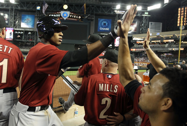 PHOENIX, AZ - AUGUST 09:  Jimmy Paredes #38 of the Houston Astros high fives teammates after scoring against the Arizona Diamondbacks during the Major League Baseball game at Chase Field on August 9, 2011 in Phoenix, Arizona.  The Diamondbacks defeated th