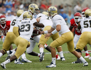 HOUSTON - SEPTEMBER 03:  Quarterback Richard Brehaut #12 of UCLA hands off to running back Johnathan Franklin #23  at Robertson Stadium on September 3, 2011 in Houston, Texas.  (Photo by Bob Levey/Getty Images)