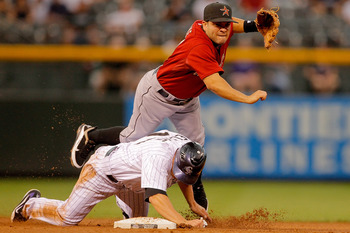 DENVER, CO - AUGUST 22:  Jose Altuve #27 of the Houston Astros is taken out at second base by Mark Ellis #14 of the Colorado Rockies during the first inning at Coors Field on August 22, 2011 in Denver, Colorado. The Rockies defeated the Astros 9-5. (Photo
