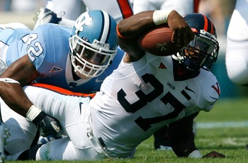 CHAPEL HILL, NC - SEPTEMBER 15:  Tailback Cedric Peerman #37 of the Virginia Cavaliers reaches for more yardage against cornerback Charles Brown #42 of the North Carolina Tar Heels during the first half of their Atlantic Coast Conference football game at