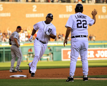 DETROIT, MI - AUGUST 15: Delmon Young #21 of the Detroit Tigers rounds third base to high-five third base coach Gene Lamont #22 after hitting a home run in the first inning on his first at bat as a Tiger against the Minnesota Twins during a MLB game at Co