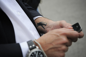 PEDRENA, SPAIN - MAY 11:  A Mourner with the iconic image of Severiano Ballestors tattooed checks his mobile phone during the funeral service held for legendary Spanish golfer Seve Ballesteros on May 11, 2011 in Pedrena, Spain. Top-ranked golf players hav