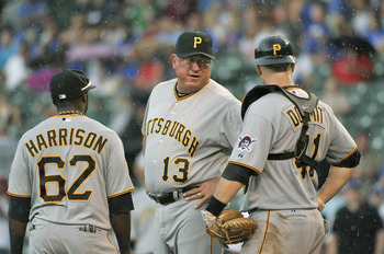 CHICAGO, IL - SEPTEMBER 03:  Manager Clint Hurdle #13 of the Pittsburgh Pirates stands on the mound with third baseman Josh Harrison #62 and catcher Ryan Doumit #41 during the seventh inning against the Chicago Cubs at Wrigley Field on September 3, 2011 i