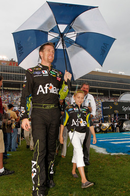 HAMPTON, GA - SEPTEMBER 04:  Carl Edwards, driver of the #99 Aflac Ford, walks with an umbrella during driver introductions prior to the NASCAR Sprint Cup Series AdvoCare 500 at Atlanta Motor Speedway on September 4, 2011 in Hampton, Georgia.  (Photo by T
