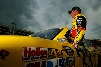 HAMPTON, GA - SEPTEMBER 03:  Clint Bowyer, driver of the #33 Cheerios/Hamburger Helper Chevrolet, climbs from his car after qualifying for the NASCAR Sprint Cup Series AdvoCare 500 at Atlanta Motor Speedway on September 3, 2011 in Hampton, Georgia.  (Phot