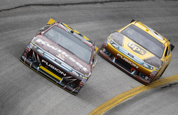 HAMPTON, GA - SEPTEMBER 06:  Marcos Ambrose, driver of the #9 Kwikset Ford, leads David Ragan, driver of the #6 UPS Ford, during the NASCAR Sprint Cup Series AdvoCare 500 at Atlanta Motor Speedway on September 6, 2011 in Hampton, Georgia.  (Photo by Todd
