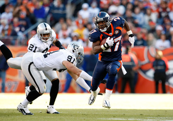 DENVER - DECEMBER 20:  Runningback Knowshon Moreno #27 of the Denver Broncos avoids a tackle from Trevor Scott #91 of the Oakland Raiders in the first half at Invesco Field at Mile High on December 20, 2009 in Denver, Colorado. The Raiders defeated the Br