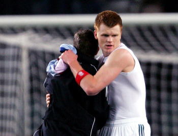 BARCELONA, SPAIN - FEBRUARY 21:  John Arne Riise of Liverpool embraces Craig Bellamy after the UEFA Champions League round of 16 first leg match between Barcelona and Liverpool at the Nou Camp Stadium on February 21, 2007 in Barcelona, Spain.  (Photo by A