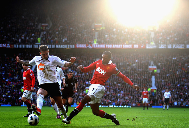 MANCHESTER, ENGLAND - MARCH 19: Patrice Evra of Manchester United battles with Gretar Rafn Steinsson of Bolton Wanderers during the Barclays Premier League match between Manchester United and Bolton Wanderers at Old Trafford on March 19, 2011 in Mancheste