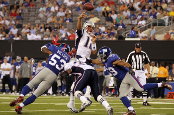 EAST RUTHERFORD, NJ - SEPTEMBER 02:  Tom Brady #12 of the New England Patriots throws a touchdown pass in the first quarter against the New York Giants to teammate Rob Gronkowski  (not pictured) on September 2, 2010 at the New Meadowlands Stadium in East