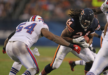 CHICAGO, IL - AUGUST 13: Marion Barber #24 of the Chicago Bears runs past Andra Davis #54 of the Buffalo Bills closes in during a preseason game at Soldier Field on August 13, 2011 in Chicago, Illinois. The Bears defeated the Bills 10-3.  (Photo by Jonath