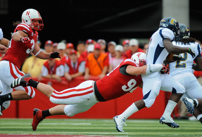LINCOLN, NE - SEPTEMBER 03: Chris Awuah #9 of the Chattanooga Mocs is brought down by Jared Crick #94 of the Nebraska Cornhuskers during their game at Memorial Stadium September 3, 2011in Lincoln, Nebraska. Nebraska won 40-7. (Photo by Eric Francis/Getty