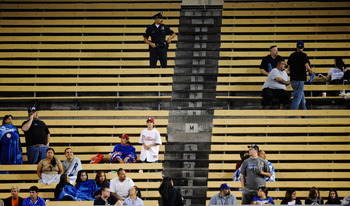 LOS ANGELES, CA - AUGUST 08:  A Los Angeles Police Department police officer looks at fans in the nearly empty right field pavillion during the basbeall between the Philadelphia Phillies and the Los Angeles Dodgers at Dodger Stadium on August 8, 2011 in L
