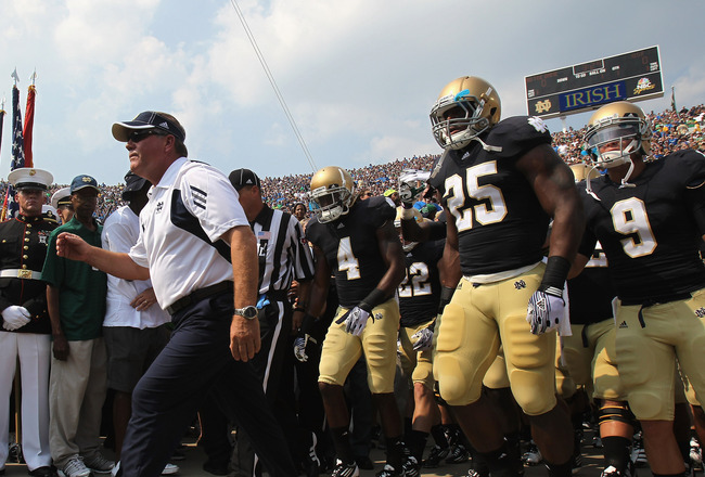SOUTH BEND, IN - SEPTEMBER 03:  Head coach Brian Kelly of the Notre Dame Fighting Irish leads his team onto the field before taking on the University of South Florida Bulls at Notre Dame Stadium on September 3, 2011 in South Bend, Indiana.  (Photo by Jona