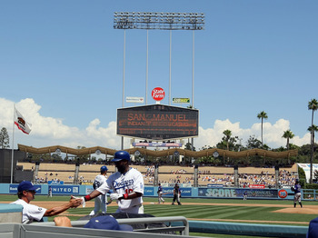 LOS ANGELES, CA - AUGUST 28:  Tony Gwynn Jr. #10 of the Los Angeles Dodgers celebrates scoring with manager Don Mattingly as Gwynn enters the dugout in the first inning during the MLB game against the Colorado Rockies at Dodger Stadium on August 28, 2011