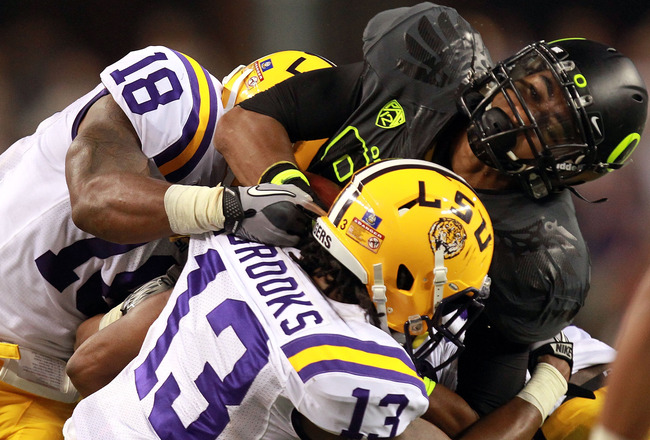 ARLINGTON, TX - SEPTEMBER 03:  Lavasier Tuinei #80 of the Oregon Ducks is tackled by Brandon Taylor #18 and Ron Brooks #13 of the LSU Tigers at Cowboys Stadium on September 3, 2011 in Arlington, Texas.  (Photo by Ronald Martinez/Getty Images)