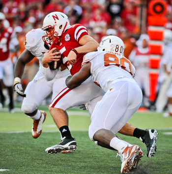 LINCOLN, NE - OCTOBER 16: Quarterback Zac Lee #5 of the Nebraska Cornhuskers gets tackled by defensive end Alex Okafor #80 of the Texas Longhorns during their game at Memorial Stadium on October 16, 2010 in Lincoln, Nebraska. Texas Defeated Nebraska 20-13