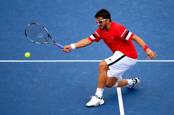NEW YORK, NY - SEPTEMBER 05:  Janko Tipsarevic of Serbia returns a shot against Juan Carlos Ferrero of Spain during Day Eight of the 2011 US Open at the USTA Billie Jean King National Tennis Center on September 5, 2011 in the Flushing neighborhood of the