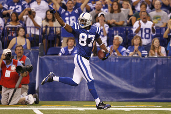 INDIANAPOLIS, IN - AUGUST 26: Reggie Wayne #87 of the Indianapolis Colts runs down the sideline on a 57-yard touchdown reception during the first half of an NFL preseason game against the Green Bay Packers at Lucas Oil Stadium on August 26, 2011 in Indian