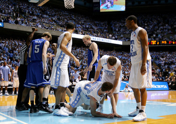 CHAPEL HILL, NC - MARCH 04:  Tyler Hansbrough is helped up by teammate Dewey Burke #15 of the University of North Carolina after Gerald Henderson #15 of the Duke Blue Devils is ejected from the game for a flagrant foul he committed on Hansbrough during th