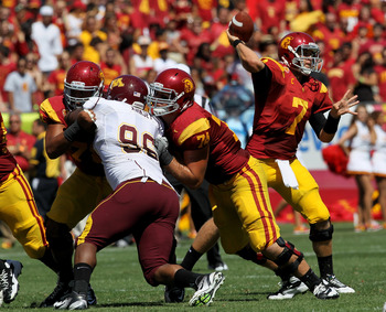 LOS ANGELES, CA - SEPTEMBER 03:  Quarterback Matt Barkley #7 of the USC Trojans throws a pass as guard Jeremy Galten #74 blocks nose tackle Brandon Kirksey #96 of the Minnesota Golden Gophers at the Los Angeles Memorial Coliseum on September 3, 2011 in Lo