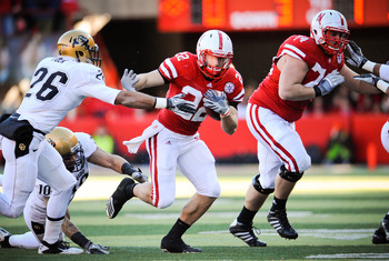 LINCOLN, NE - NOVEMBER 26: Rex Burkhead #22 of the Nebraska Cornhuskers slips past Ray Polk #26 of the Colorado Buffaloes during their game at Memorial Stadium on November 26, 2010 in Lincoln, Nebraska. Nebraska defeated Colorado 45-17 (Photo by Eric Fran