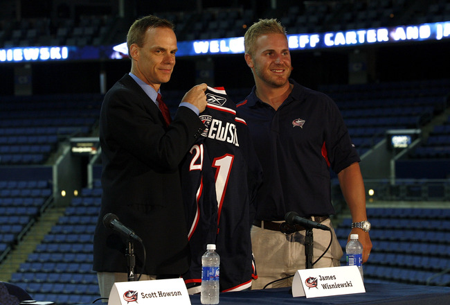 COLUMBUS,OH - JULY 21:  Columbus Blue Jackets General Manager Scott Howson presents James Wisniewski #21 of the Columbus Blue Jackets a jersey during a press conference on July 21, 2011 at Nationwide Arena in Columbus, Ohio.  (Photo by John Grieshop/Getty