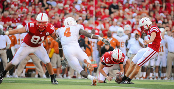 LINCOLN, NE - OCTOBER 16: Kicker Alex Henery #90 of the Nebraska Cornhuskers kicks a ball held by teammate  Brett Maher #96 during their game at Memorial Stadium on October 16, 2010 in Lincoln, Nebraska. Texas Defeated Nebraska 20-13. (Photo by Eric Franc