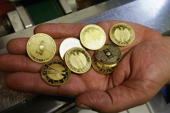 BERLIN, GERMANY - APRIL 28: A worker shows some of the first 100 Euro gold soccer coins on April 28, 2005 in Berlin, Germany. The Federal Republic of Germany issued a Euro 100 gold coin on the theme of the 2006 FIFA World Cup in Germany.  (Photo by Carste