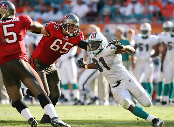 MIAMI GARDENS, FL - NOVEMBER 15:  Tackle Jeremy Trueblood #65 of the Tampa Bay Buccaneers tries to keep linebcker Cameron Wake #91 of the Miami Dolphins from getting to quarterback Josh Freeman #5 at Land Shark Stadium on November 15, 2009 in Miami Garden