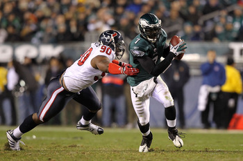 PHILADELPHIA, PA - DECEMBER 02:  Michael Vick #7 of the Philadelphia Eagles runs with the ball as he elludes the pass rush from Mario Williams #90 of the Houston Texans at Lincoln Financial Field on December 2, 2010 in Philadelphia, Pennsylvania.  (Photo
