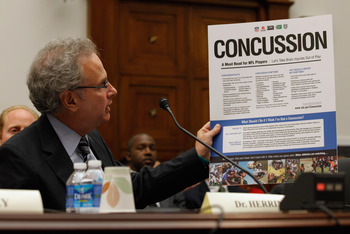 WASHINGTON - SEPTEMBER 23:  Stanley Herring, chairman of the Subcommittee on Education and Advocacy, Head, Neck and Spine Committee of the NFL and team physician for the Seattle Seahawks and Seattle Mariners, holds up a Centers for Disease Control poster