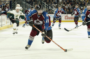 DENVER - APRIL 9:  Peter Forsberg #21 of the Colorado Avalanche breaks away against the Dallas Stars in the third period of game two of the first round of the Stanley Cup playoffs at the Pepsi Center on April 9, 2004 in Denver, Colorado.  The Avs won 5-2.