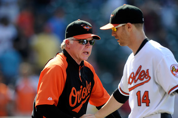 BALTIMORE, MD - AUGUST 14:  Manager Buck Showalter congratulates Nolan Reimold #14 of the Baltimore Orioles  after a 8-5 victory against the Detroit Tigers at Oriole Park at Camden Yards on August 14, 2011 in Baltimore, Maryland.  (Photo by Greg Fiume/Get