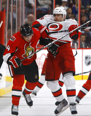 OTTAWA, ON - OCTOBER 14:  Chris Phillips #4 of the Ottawa Senators takes a hit from Tuomo Ruutu #15 of the Carolina Hurricanes during a game at Scotiabank Place on October 14, 2010 in Ottawa, Ontario, Canada.  The Ottawa Senators defeated the Carolina Hur