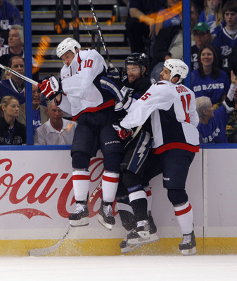 TAMPA, FL - MAY 03: Dominic Moore #19 of the Tampa Bay Lightning is hit by Matt Bradley #10 and Boyd Gordon #15 of the Washington Capitals in Game Three of the Eastern Conference Semifinals during the 2011 NHL Stanley Cup Playoffs at St Pete Times Forum o
