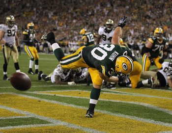 GREEN BAY, WI - SEPTEMBER 08:  John Kuhn #30 of the Green Bay Packers spikes the ball after scoring a touchdown against the New Orleans Saints during the NFL opening season game at Lambeau Field on September 8, 2011 in Green Bay, Wisconsin.  (Photo by Jon