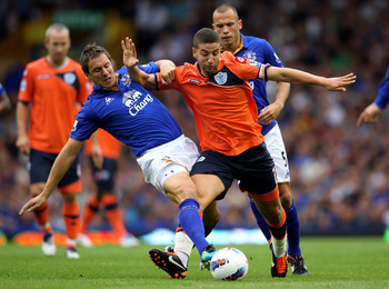 LIVERPOOL, ENGLAND - AUGUST 20:  Phil Jagielka of Everton challenges Adel Taarabat of Queens Park Rangers during the Barclays Premier League match between Everton and Queens Park Rangers at Goodison Park on August 20, 2011 in Liverpool, England.  (Photo b