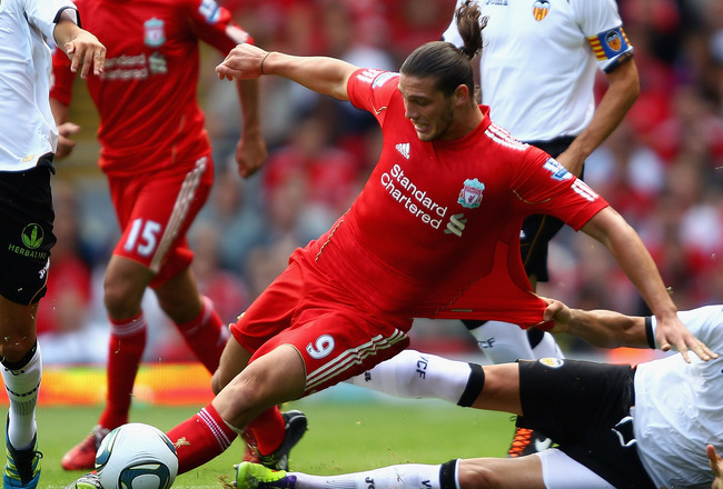 LIVERPOOL, ENGLAND - AUGUST 06:  Andy Carroll of Liverpool in action with Adil Rami of Valencia during the pre season friendly match between Liverpool and Valencia at Anfield on August 6, 2011 in Liverpool, England.  (Photo by Clive Brunskill/Getty Images