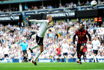 LONDON, ENGLAND - AUGUST 28:  Peter Crouch of Tottenham heads the ball wide as Joleon Lescott of Manchester City looks on during the Barclays Premier League match between Tottenham Hotspur and Manchester City at White Hart Lane on August 28, 2011 in Londo