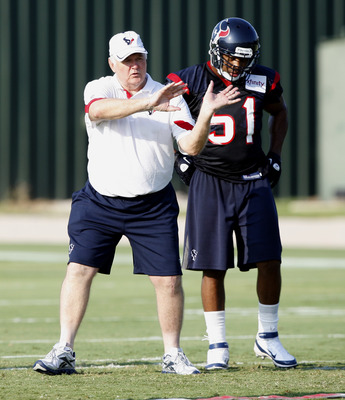 HOUSTON, TX - AUGUST 01:  Defensive Coordinator Wade Phillips of the Houston Texans goes over plays with inside linebacker Darryl Sharpton #51 during practice on the first day of training camp at Reliant Park on August 1, 2011 in Houston, Texas.  (Photo b