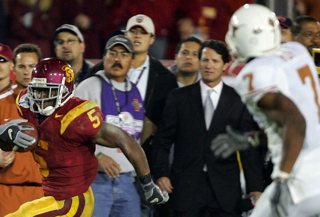PASADENA, CA - JANUARY 04:  Reggie Bush #5 of the USC Trojans runs along the sidelines past  Michael Huff #7 of the Texas Longhorns en route to scoring a 26 yard touchdown in the fourth quarter of the BCS National Championship Rose Bowl Game at the Rose B
