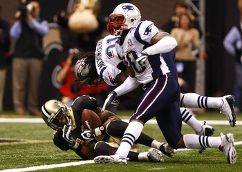 NEW ORLEANS - NOVEMBER 30: Marques Colston #12 of the New Orleans Saints catches a 20-yard touchdown reception in the fourth quarter against Brandon McGowan #30 and Brandon Meriweather #31 of the New England Patriots at Louisana Superdome on November 30,