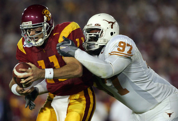 PASADENA, CA - JANUARY 04:  Quarterback Matt Leinart #11 of the USC Trojans is sacked by Frank Okam #97 of the Texas Longhorns during the second quarter of the BCS National Championship Rose Bowl Game at the Rose Bowl on January 4, 2006 in Pasadena, Calif