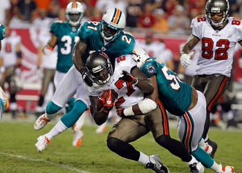 TAMPA, FL - AUGUST 27:  Running back LeGarrette Blount #27 of the Tampa Bay Buccaneers is tackled by defenders Karlos Dansby #58 and Vontae Davis #21 of the Miami Dolphins during a preseason game at Raymond James Stadium on August 27, 2011 in Tampa, Flori