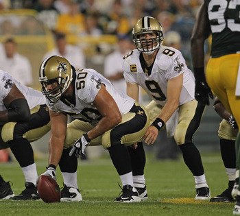 GREEN BAY, WI - SEPTEMBER 08:  Olin Kreutz #50 of the New Orleans Saints prepares to snap the ball to Drew Brees #9 against the Green Bay Packers during the NFL opening season game at Lambeau Field on September 8, 2011 in Green Bay, Wisconsin.  (Photo by